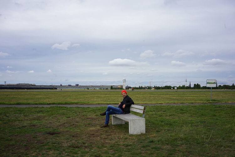 Man sitting on bench on field against sky