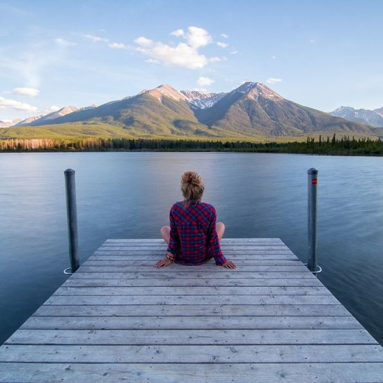Mountain Lake Scenics Adult Landscape Adults Only Water Rear View Sitting Pier Zen-like Mountain Range Only Women Nature One Person People Autumn Beauty In Nature Relaxation One Woman Only