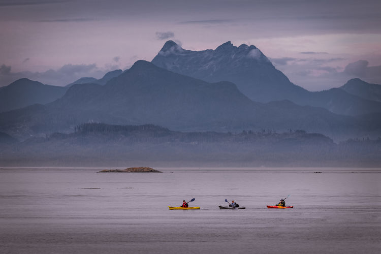 People Kayaking In Lake Against Mountains During Winter