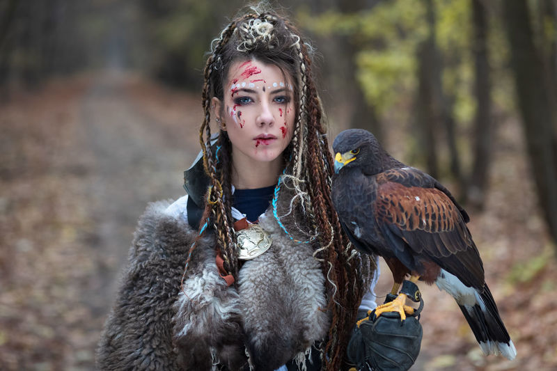 Beautiful Viking warrior woman in woods wearing fur collar, braided hair and specific makeup with face covered in blood holding hawk in hand. Northern woman with her predator in forest Woman Warrior Viking Beaautiful Princess Hawk Falcon Bird Of Prey Portrait One Person Fur Braided Hair Makeup Blood Face Bird Looking At Camera Day Forest Young Nature Hairstyle Lifestyles Woods Cinematic