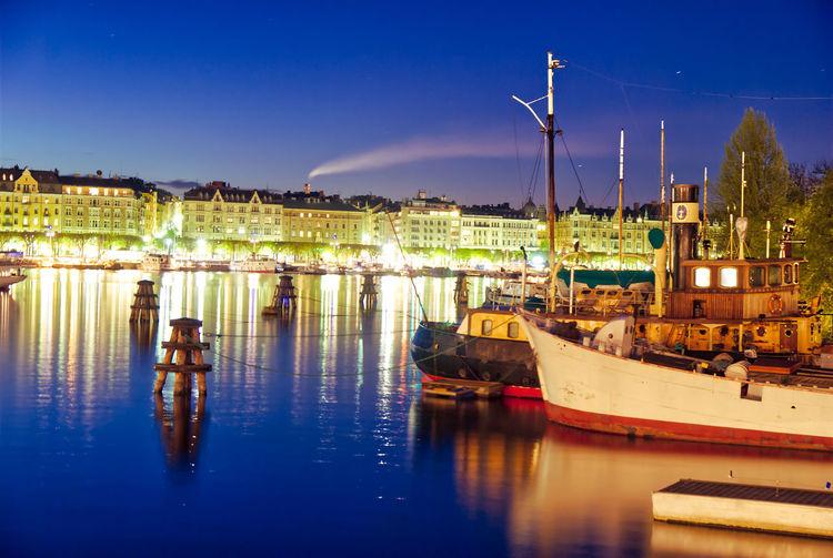 Sailboats moored at illuminated harbor against sky