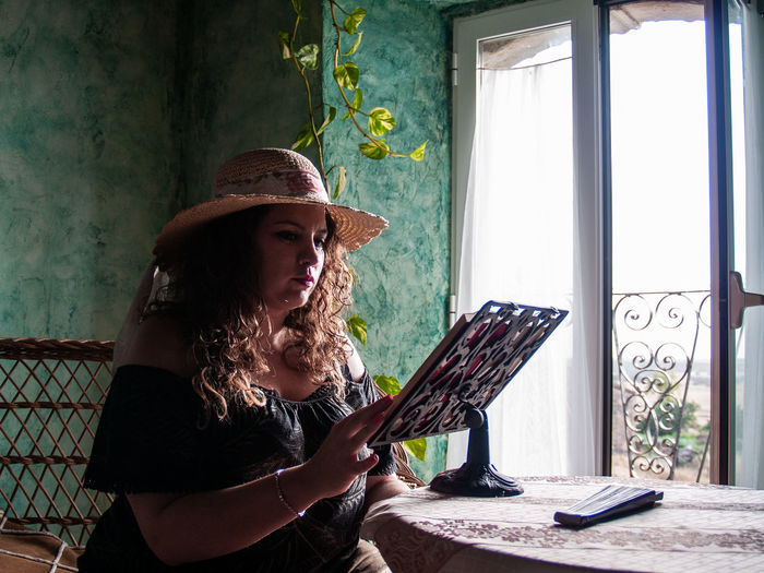 Woman Reading Book On Table At Home