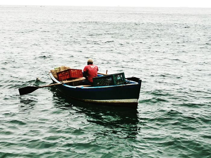 Rear view of man in boat at sea