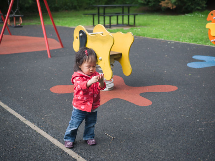 Full length of girl standing by spring ride at playground