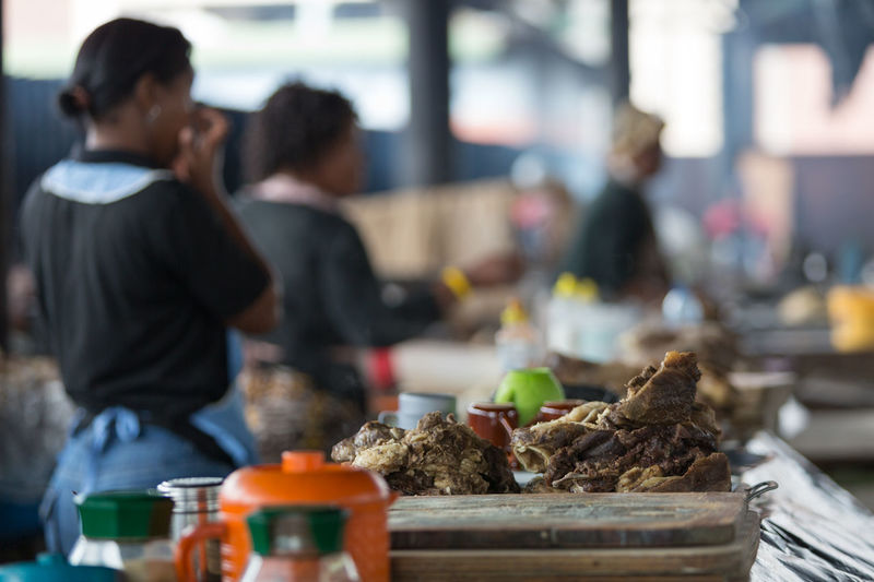 A pile of cooked meat lies on a table in a market in Warwick Junction, Durban, South Africa. Casual Clothing Cooking Day Eating Focus On Foreground Food Freshness Leisure Activity Lifestyles Market Meat Preparation  Restaurant Sale Selective Focus Sitting
