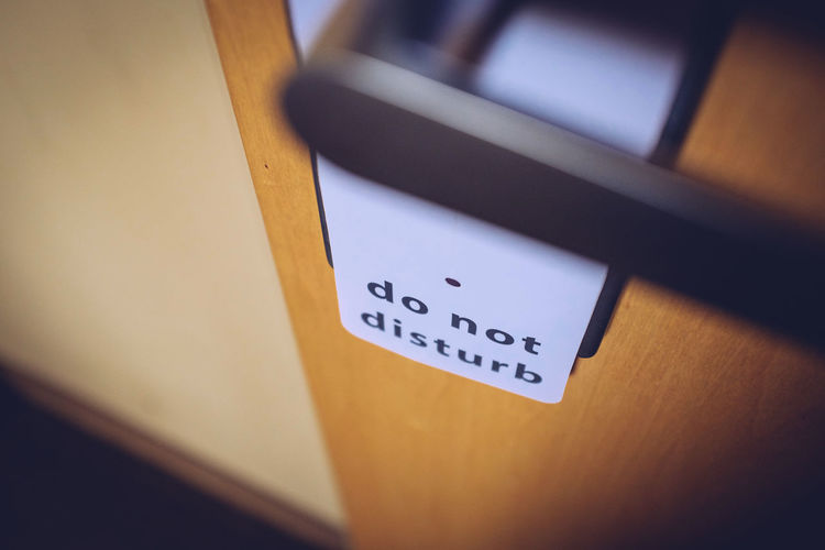 High angle view of do not disturb sign hanging on door
