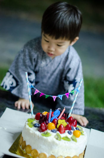 Baby boy with birthday cake on table