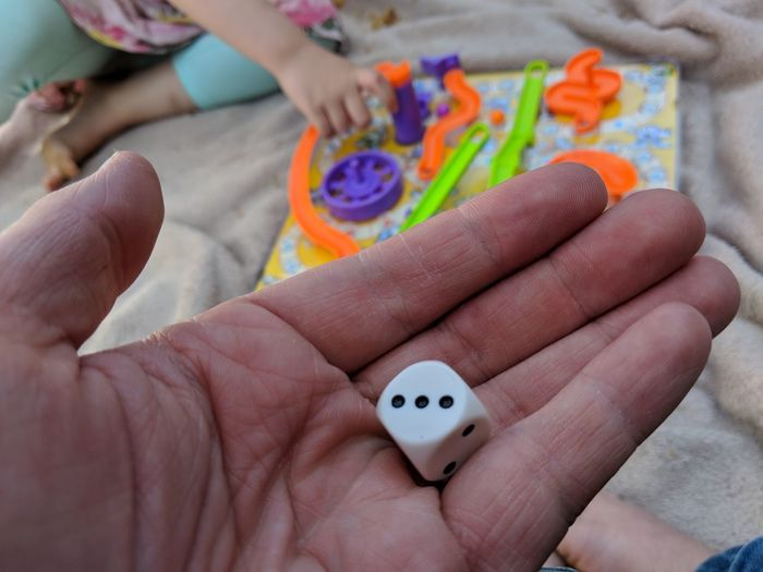 Cropped hand holding dice at beach
