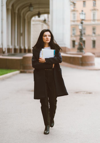 Full length of young woman with books walking outside university