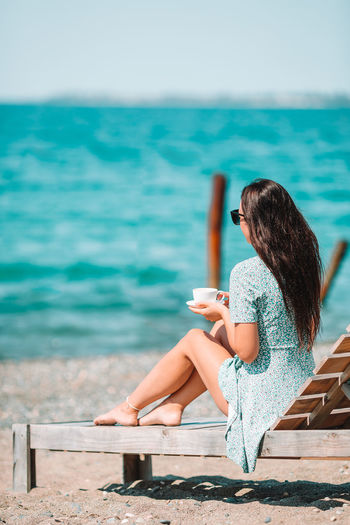 Rear view of woman holding coffee cup sitting at beach