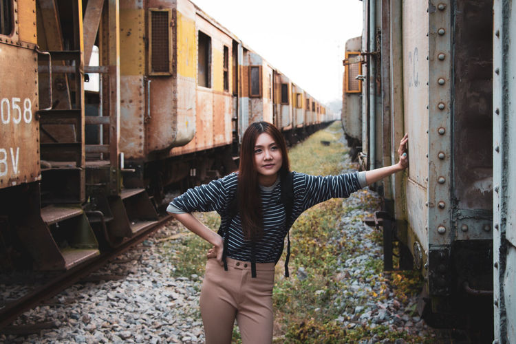 Young woman looking away while standing by train
