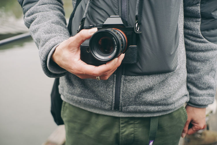 Adult Adults Only Camera - Photographic Equipment Casual Clothing Close-up Day Expertise Holding Human Hand Lens - Eye Men Midsection Old-fashioned One Man Only One Person Only Men Outdoors People Photographer Photographing Photography Themes SLR Camera Standing Technology Young Adult