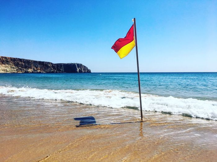 Red/Yellow Nature No People Beachphotography Wave Yellow Red Cliff Portugal Algarve Sagres Praia Da Mareta Flag Water Sea Sky Beach Land Horizon Over Water Beauty In Nature