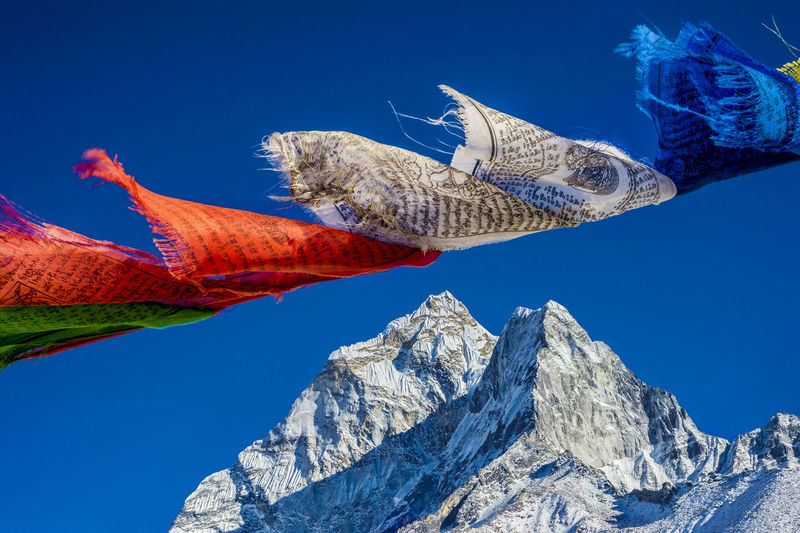 Low angle view of prayer flags and snowcapped mountain against clear blue sky