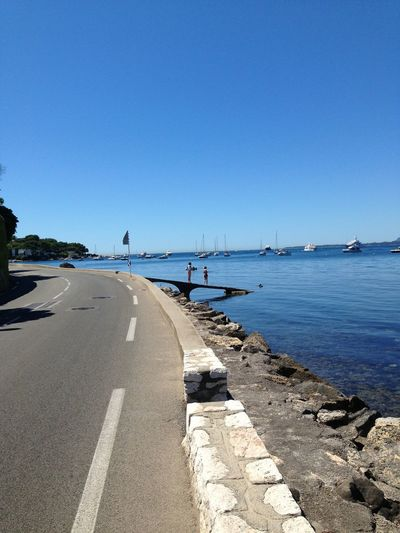 Sea by road against clear blue sky