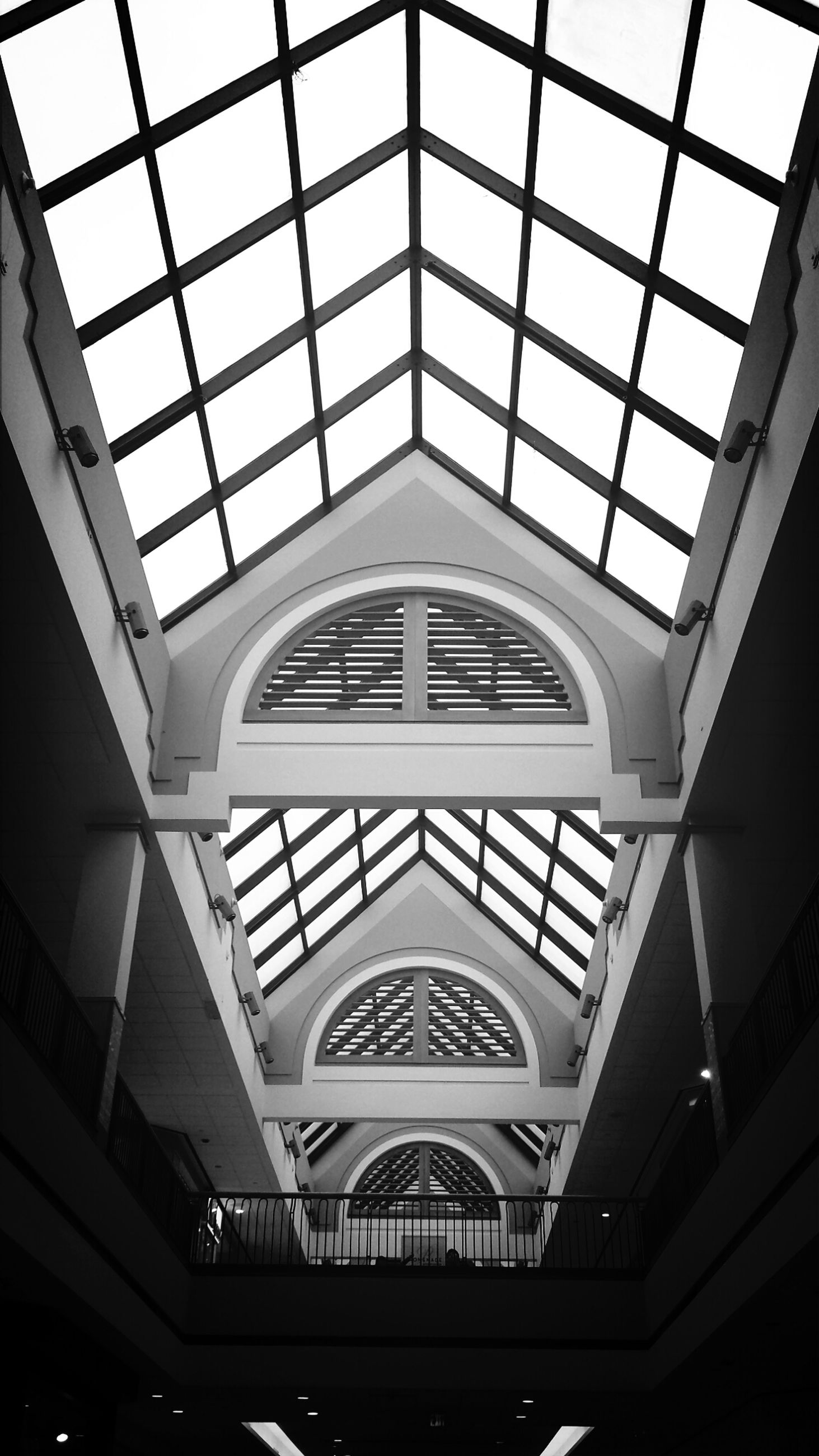 indoors, ceiling, architecture, built structure, low angle view, skylight, glass - material, window, architectural feature, modern, interior, transparent, pattern, design, directly below, building, glass, no people, day, geometric shape