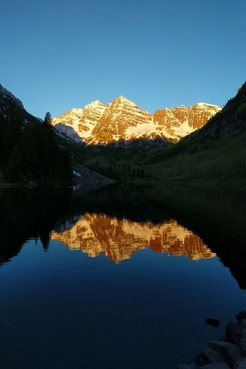 Maroon Bells Sunrise Elk Mountains Snowmass Wilderness Colorado Rockies Maroon Bells Sunrise Water Symmetry Lake Mountain Reflection Clear Sky Standing Water Sky Reflection Lake Rocky Mountains Physical Geography Natural Landmark Idyllic Scenics Snowcapped Mountain Mountain Range Tranquil Scene