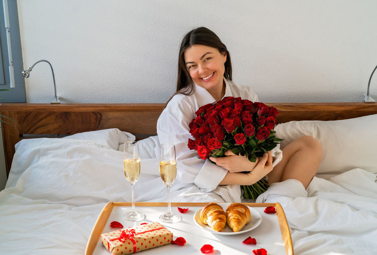 Portrait of a smiling young woman sitting on bed
