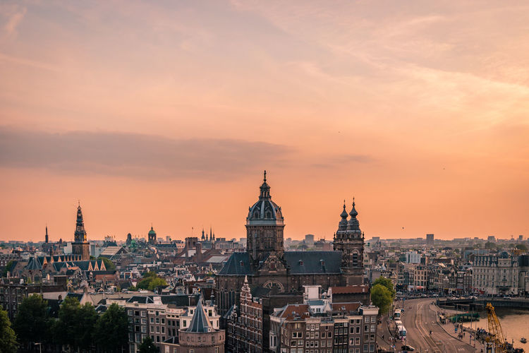 View of buildings in city against sky during sunset amsterdam
