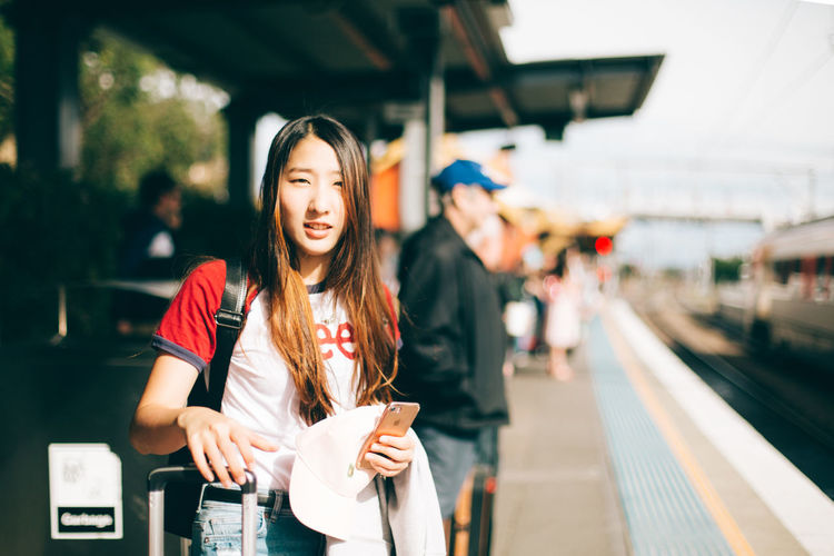 Young woman standing on railroad station platform