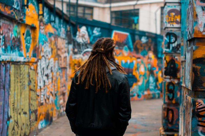 Roaming Real People One Person Graffiti Leisure Activity Rear View Lifestyles Clothing Focus On Foreground Street Art Wall - Building Feature Casual Clothing Adult Hair Hairstyle Architecture Outdoors Standing