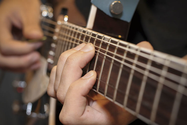 Midsection of person playing guitar
