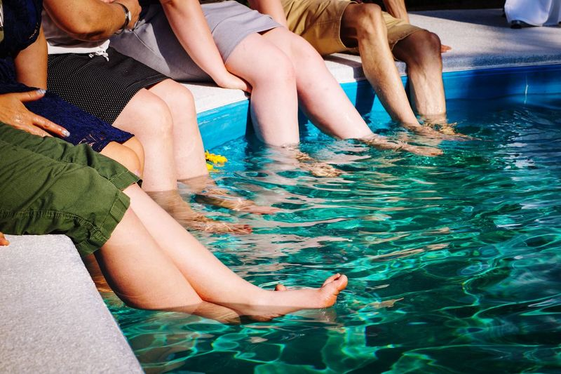 Low section of people sitting in swimming pool