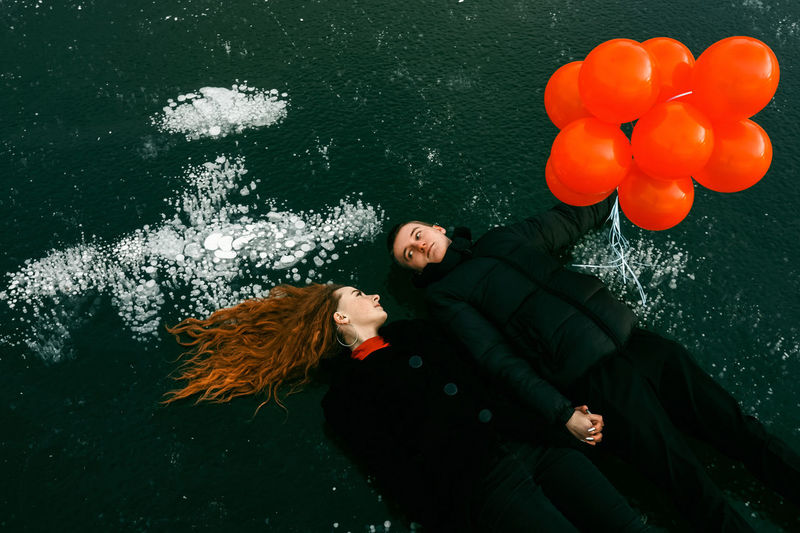 High angle view of couple with balloons lying on land