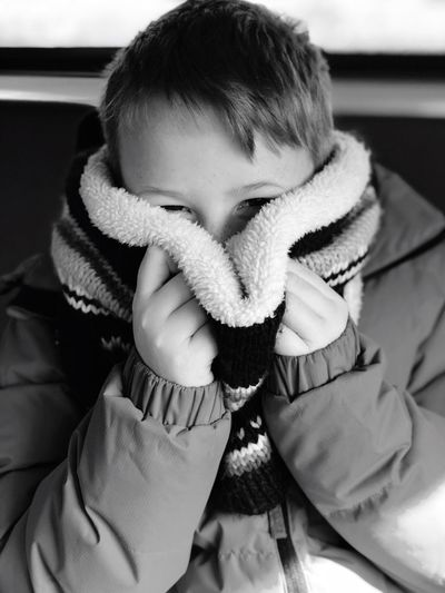 Close-up portrait of cute boy covering face