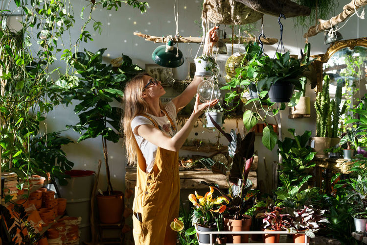 Woman standing by potted plants