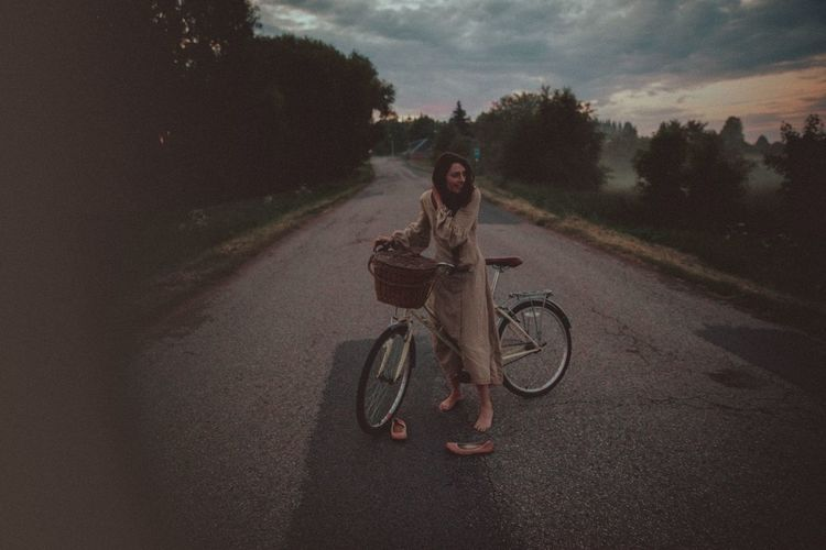 Portrait of women riding bicycle on road