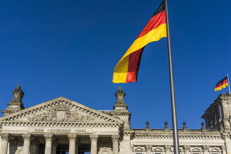 Low angle view of german flag on reichstag building against clear blue sky during sunny day