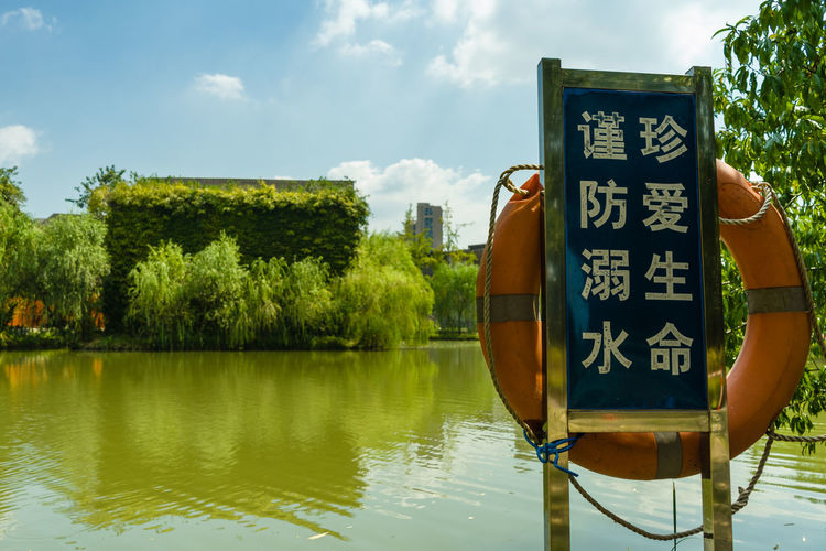 Information sign by lake against sky