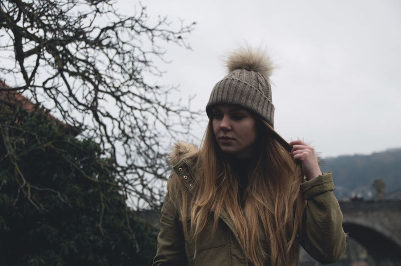Young woman wearing knit hat while walking by bare trees against sky
