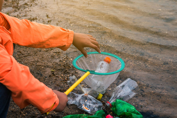 Low section of volunteer removing plastic bottles from lake