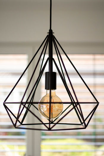Close-up of lamp hanging on table at home