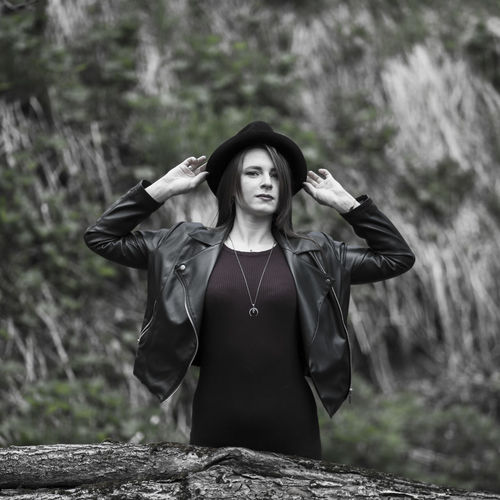 Portrait of young woman wearing hat standing in forest