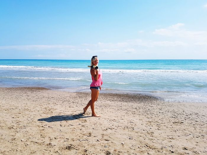 Woman holding champagne bottle standing on beach against clear blue sky