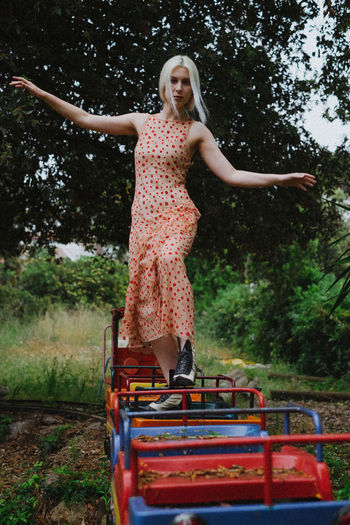 Young Woman Standing On Miniature Train