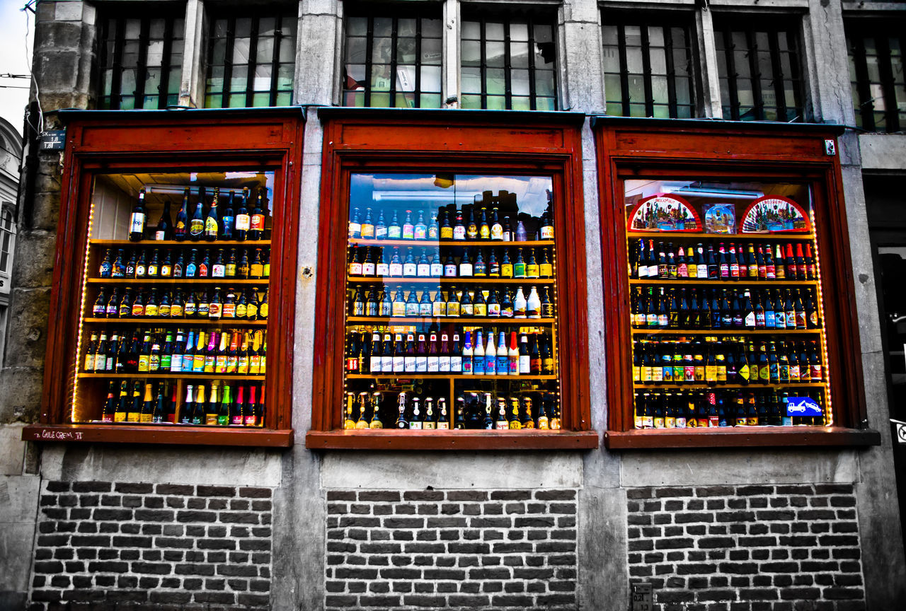 shelf, bookshelf, arrangement, large group of objects, indoors, architecture, no people, window, variation, day, built structure, choice, alcohol, multi colored, library, close-up