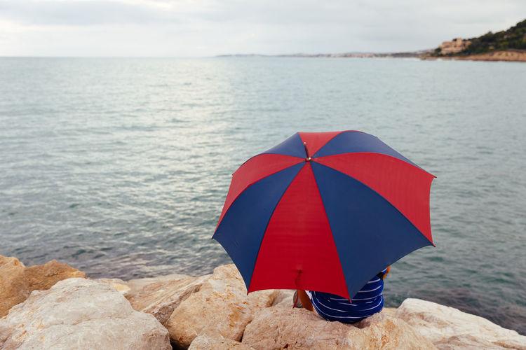 Red umbrella on rock at beach
