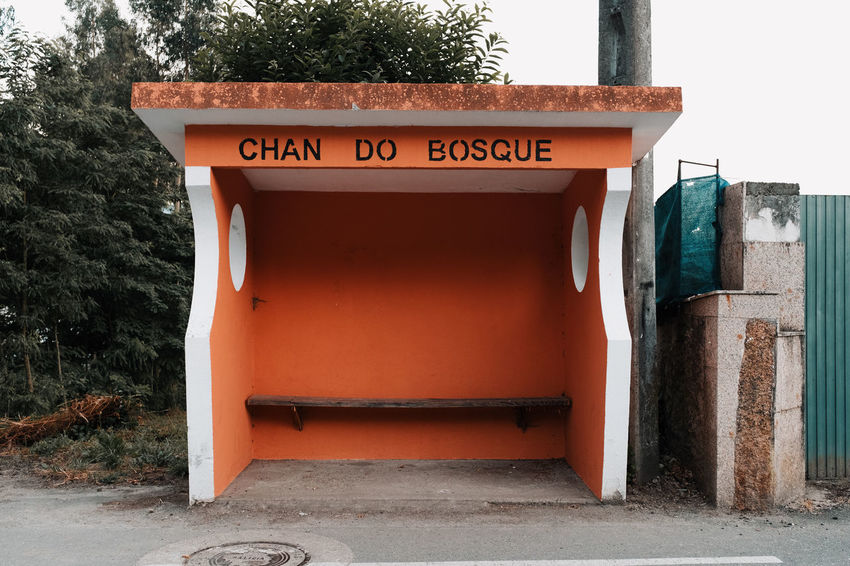 LOST IN GALICIA 🚌 Lostingalicia Bus Stop Threeweeksgalicia Text Communication Architecture Western Script Built Structure No People Day Orange Color Tree Building Exterior Script Non-western Script Sign Outdoors Red Entrance Wall - Building Feature Plant Nature Information