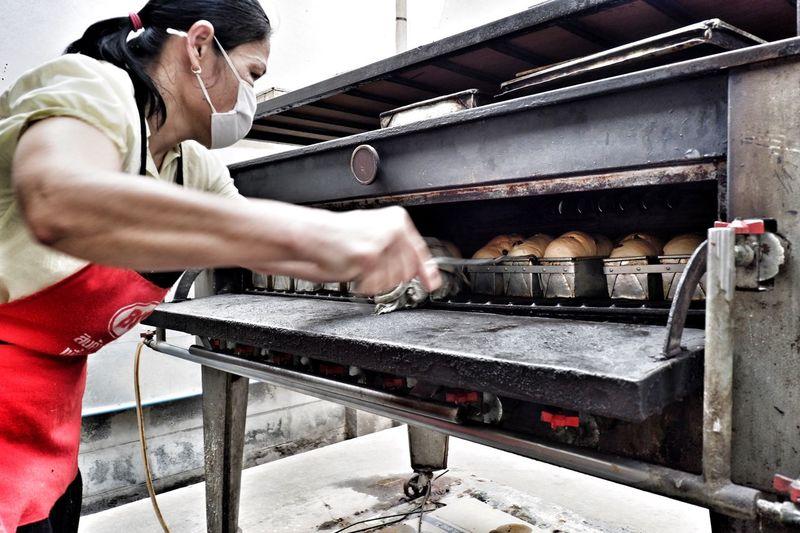 Woman preparing food in oven at restaurant