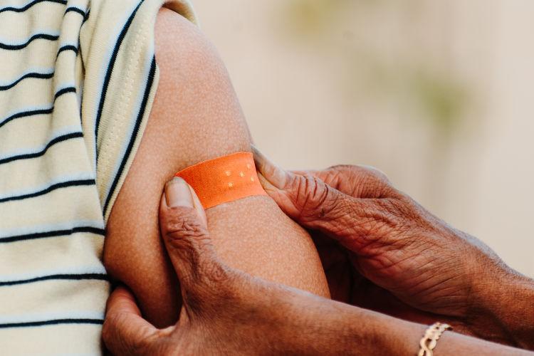 Woman sticking bandage on arm