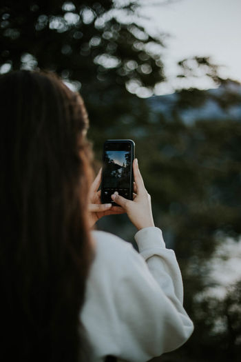 Rear view of woman photographing through smart phone