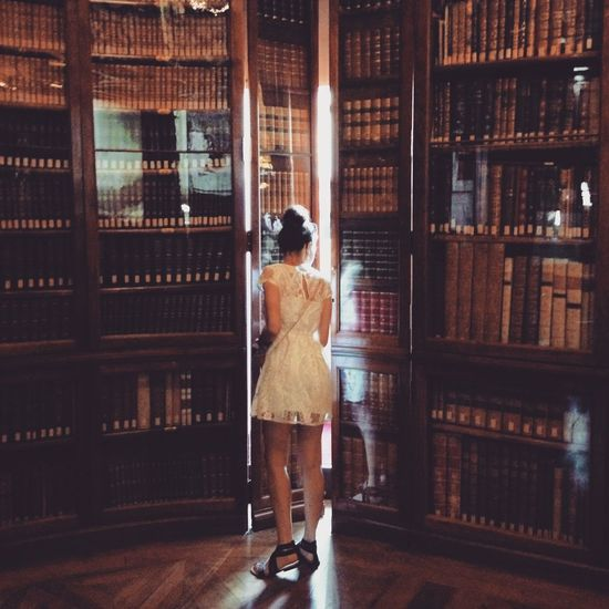 Woman standing against bookshelf in library