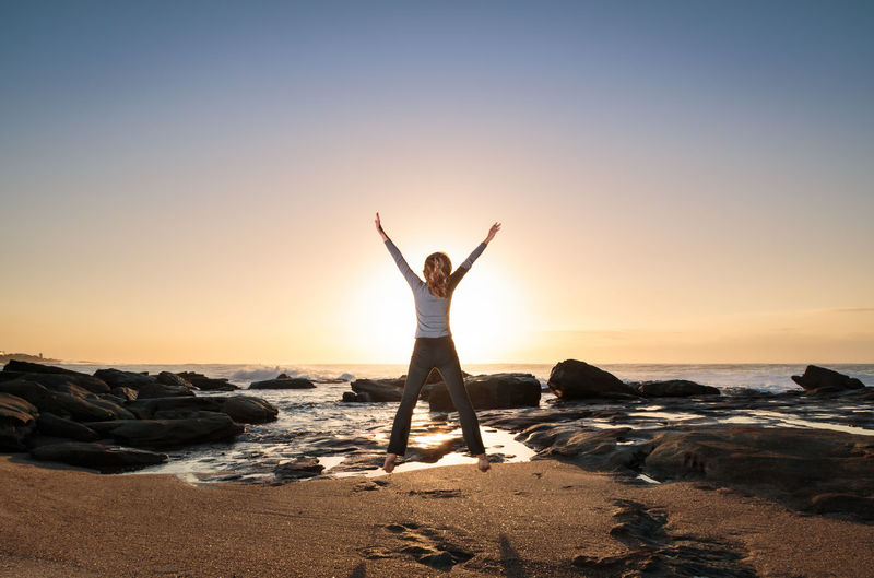 Rear view of excited woman jumping over beach against sky during sunrise