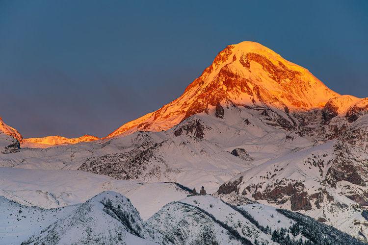 View of caucasus mountains, gergeti trinity church tsminda sameba and sunlight landmark of georgia