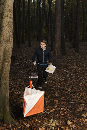 Teenager running in a orienteering competition. Selective focus Outdoors Sport Orienteering Navigation Compass Activity Competition Forest Caucasian Teenager Flag Chip Time Running Cross Map Skills  Experience Rules Discover  Leisure Activity Check Number Boy One Person
