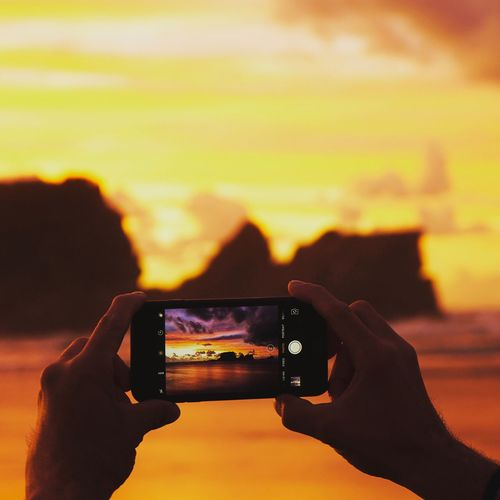 Photography Themes Photographing Human Hand Smart Phone Wireless Technology Real People Holding Portable Information Device Mobile Phone Technology One Person Camera - Photographic Equipment Digital Camera Sunset Leisure Activity Photo Messaging Lifestyles Screen Leisure Human Body Part